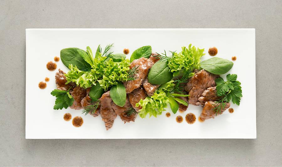 Kambodschanisches Beef Lok Lak nachkochen und genießen: Zarte Rindfleischstreifen in würziger Soße mit frischen Kräutern und aromatischem Dip.